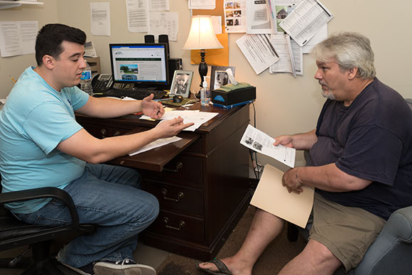Peter Katsilis LSW, helps Robert Dawson with income based housing at The May Dugan Center