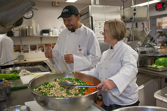 Case Manager Shelly Bishop workis with Erik Wells, trainee in the Vocational Training Center program in Cornucopia's state-of-the-art commercial kitchen