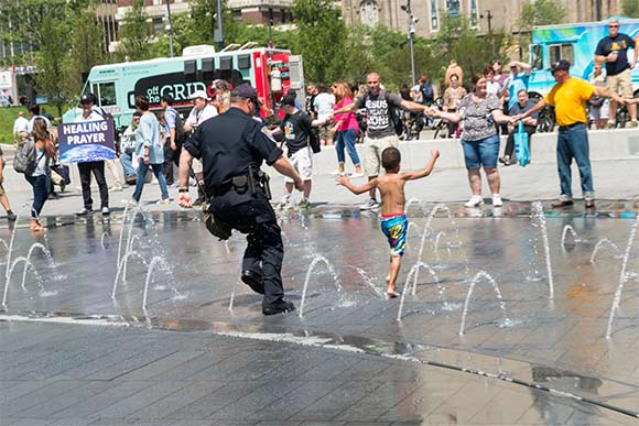 An Indiana officer runs with a local child through the fountain in Public Square