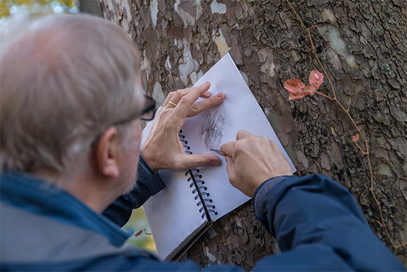 Douglas Paige making a tree bark rubbing in his field notebook