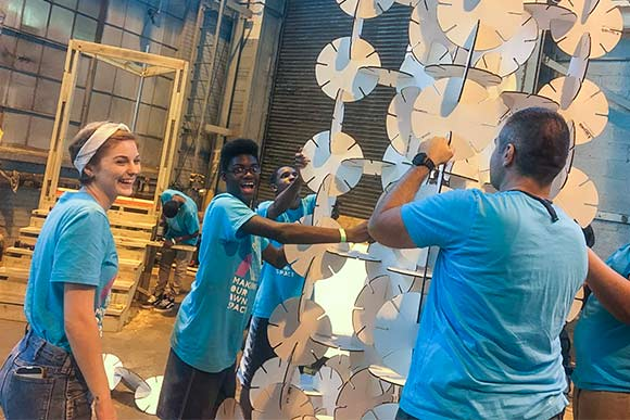 (MOOS) kids at IngenuityFest making towering art sculptures out of interlocking would-be flower discs