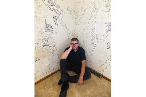 Derf by the mural he drew on the walls of his bedroom as a teen