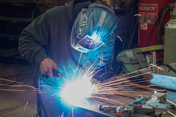 As his MIG welder whirrs, a masked Mazurowski is enveloped in a halo of sparks