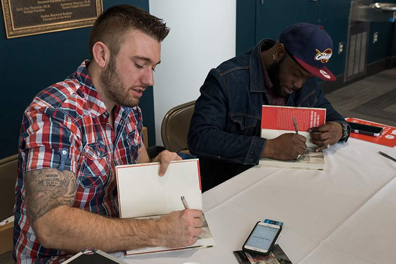 Andrew Collins and Jameel McGee signing their book: Convicted