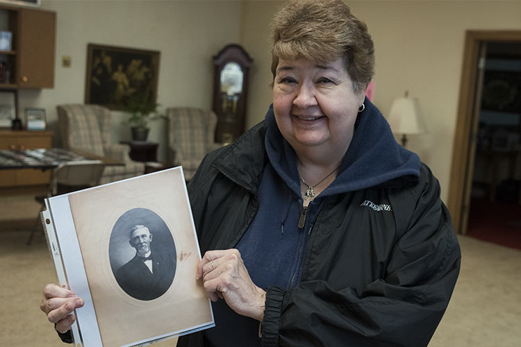 Lou Goodwin holding a photo of her grandfather, Leonard Fish