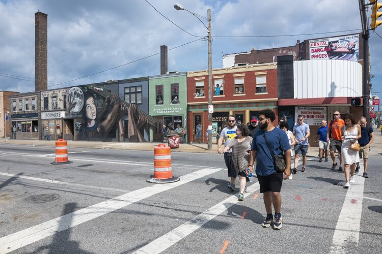 Metro West Community Development Organization's Ricardo Leon leads the walking tour past the It's Up to Us mural on Clark Avenue and West 25th Street.