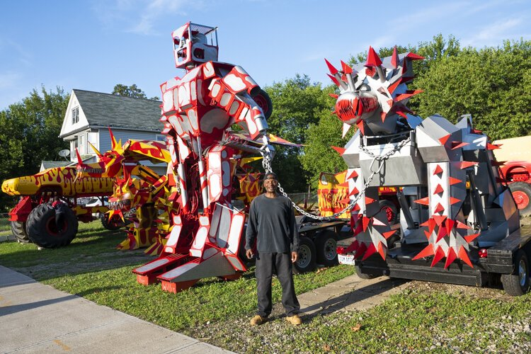 Red and yellow monster trucks and silver robots tower over the lot of automotive innovator Tim Willis.