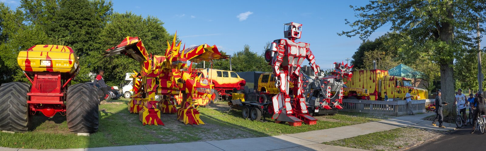 Red and yellow monster trucks and silver robots tower over the lot of Tim Willis
