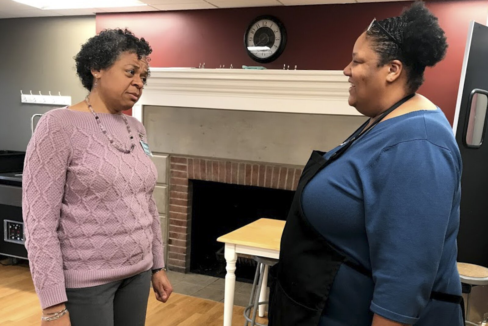 Jacqui Miller, principal of Stonebrook Montessori in Cleveland's Glenville neighborhood, talks with kitchen manager Pamela Harris. Miller is moving into a rehabbed home in Glenville.