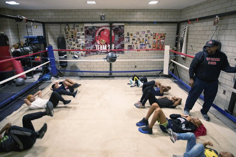 Boxers warm up with yoga and breathing exercises before moving along to boxing instruction.