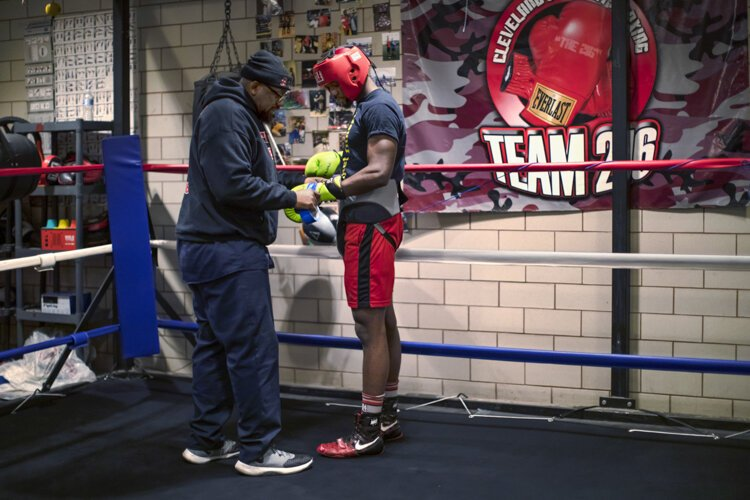 "Coach Fred helps his 25-year-old son, ""Dynomite"" Fred Wilson Jr., with his gloves before a sparring match with a boxer from Akron."