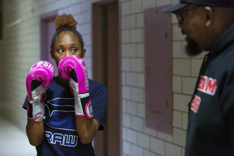 Naarae, new to the Team 216 program, learns boxing basics from Coach Fred.