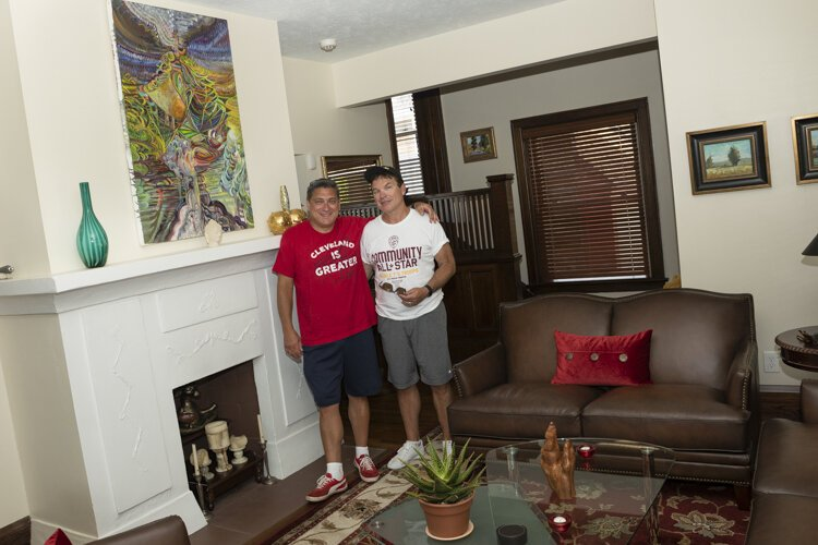 Todd and Dane in their living room with their favorite painting by a good friend in Pittsburgh