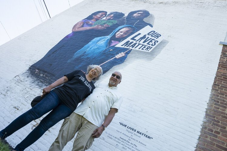 "Gary Williams and Robin Robinson with ""Our Lives Matter,"" a mural at East 105th St. and Yale Ave."