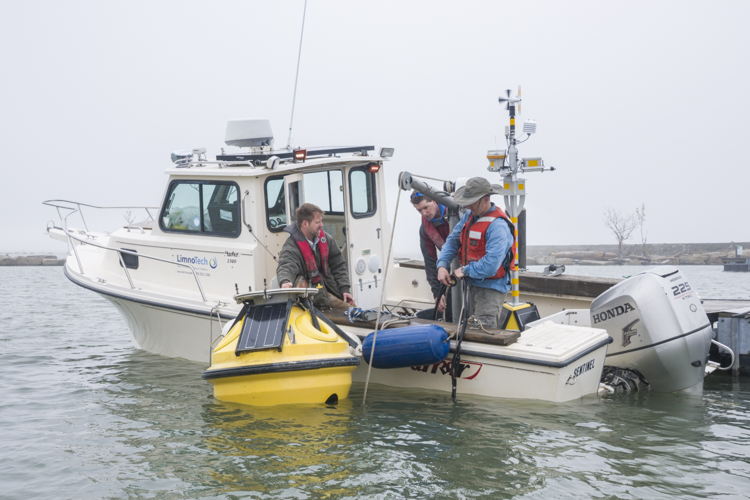 LimnoTech Project Engineer Ed Verhamme, engineer Brandon Ellefson and scientist Greg Cutrell prepare the buoy to be taken out to it's permanent location on the lake