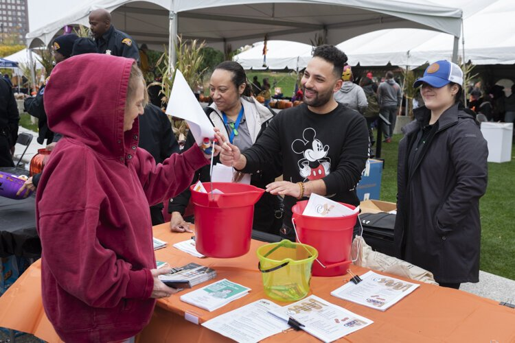 City of Cleveland Department of Public Health worker Abraham Enais gives out a lead poisoning cleanup bucket of supplies at a recent event in Public Square.