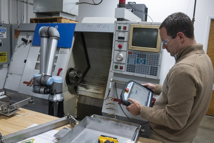 Matthew Fieldman, vice president of external affairs for MAGNET, operates a collaborative robot that eliminates boring, repetitive, and generally low-skilled jobs, letting people focus on more challenging work.