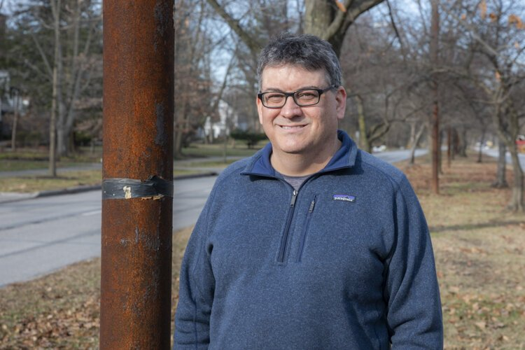 Brad Masi poses next to one of the old streetcar poles still standing on Fairmount Boulevard in Cleveland Heights.