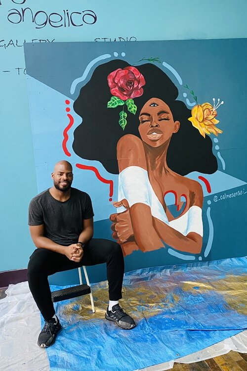 Artist Rashaun Dillard with his mural at the 5th Street Arcades.