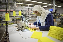 Nadia Akhlif sews a mask at National Safety Apparel as part of the company's pivot to creating face masks and gowns to fight the coronavirus.