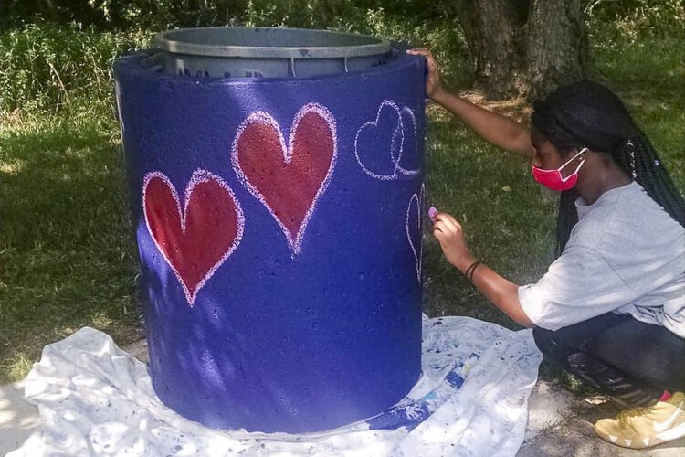Teenagers in the Youth Opportunities Unlimited employment program doing beautification projects in the neighborhood.