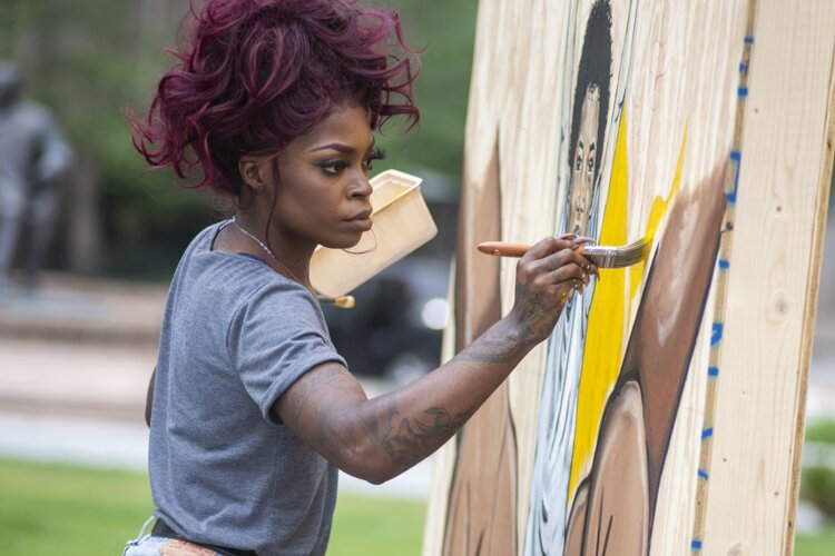 Artist Stina Aleah painting in Public Square for LAND studio's Voices of CLE exhibit.