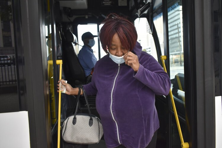 Gail Cox, of Tremont, gets off a Greater Cleveland RTA bus after it arrives in downtown Cleveland where she works as a cashier at a store nearby and uses the bus regularly during the pandemic, despite her concerns that other riders do not always wear