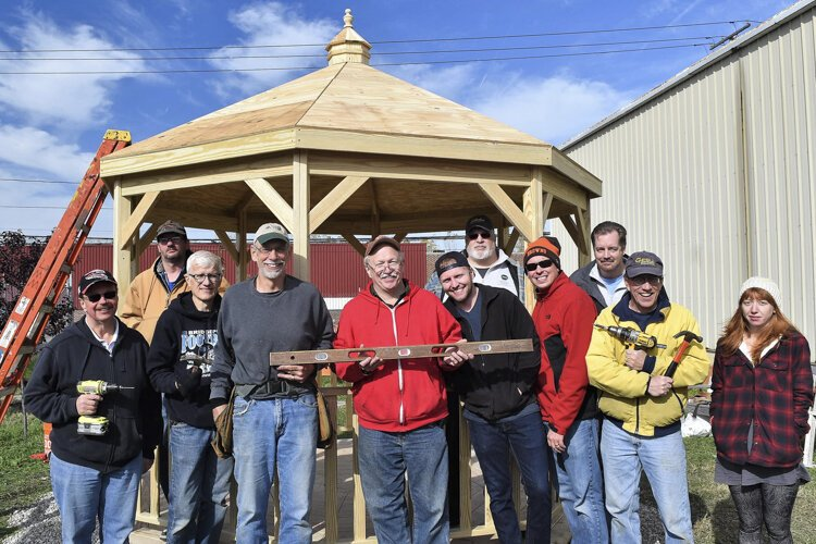 Michael Sering with staff and volunteers finishing gazebo construction at the greenspace for the guys, next to the shelter, on a Landbank donated plot.