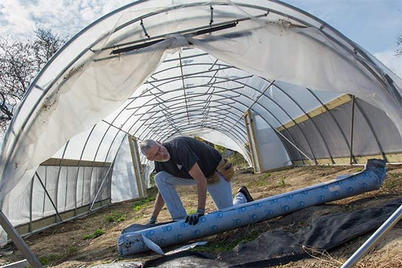 Carlton Jackson of Tunnel Vision Hoops working on a hoop house in Ohio City
