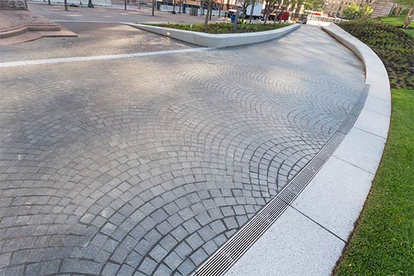 The promenade is made up of granite cobblestones in an infinite arcing pattern that winds throughout the square