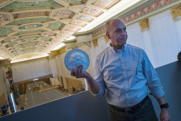 Tom Einhouse with a plaster casting of  one of the ornamental fixtures used in the ceiling