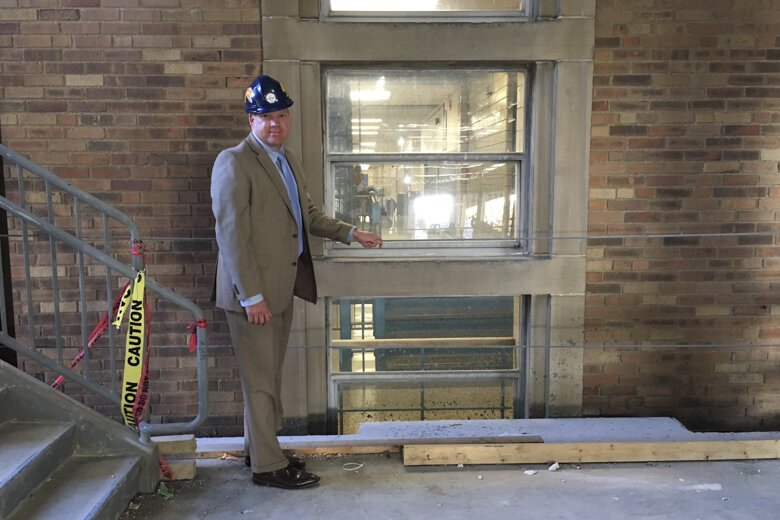 Pat Higley stands between old construction and new construction on the EHS site.