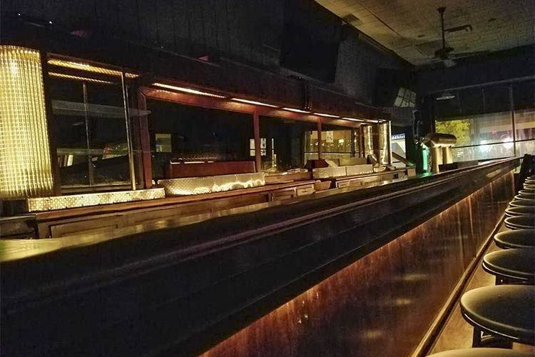 Behind the bar, the vintage lighting glows and highlights the refinished bar