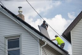 Workers install solar panels to the roof of a residential home.