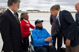 Stanley Tolliver Sr., in a wheelchair, shakes hands with President Barack Obama. Cleveland Mayor Frank Jackson is at left, and Vice President Joe Biden is at right.