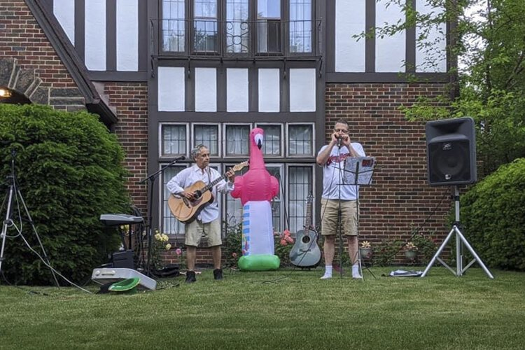 John Thayer plays with childhood friend Mitchell Cronig in an outdoor concert.