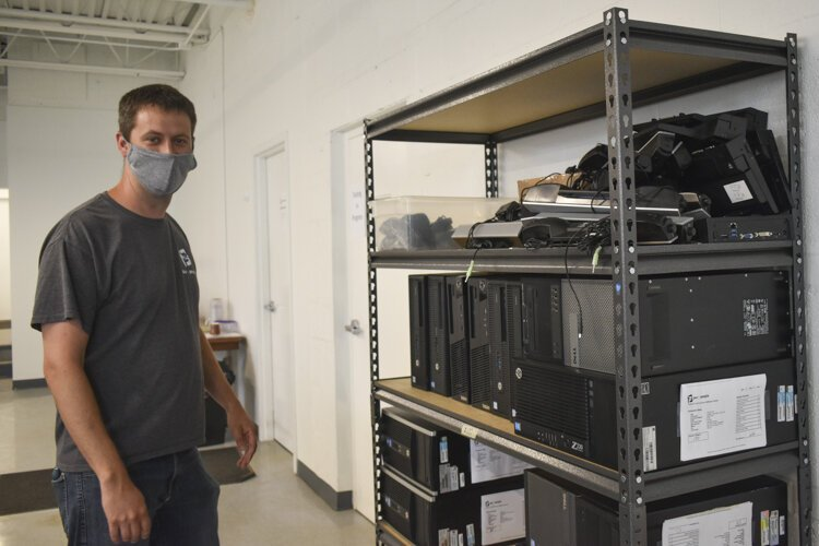 Bryan Mauk, executive director for the nonprofit PCs for People, stands near a shelf that holds computers that people can get for low- or no cost.
