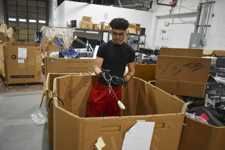 Jovanti Ramirez, a student at CMSD who has a summer internship with PCs for People, works to sort mice and other devices out of a bin in their warehouse.