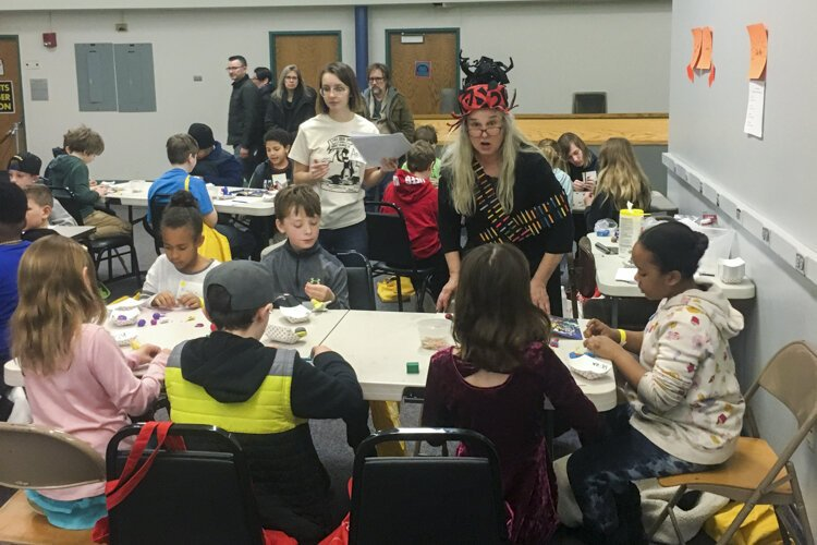 Vivian Vail, in the red and black hat, a creative arts teacher at Lake Erie Ink, oversees activities at Kids' Comic Con.