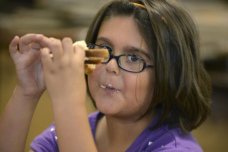 A child enjoys her sandwich at the summer lunch and enrichment program for kids initiated by the Lakewood Community Services Center for kindergarten through fifth graders.