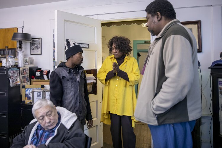 Angelina, a member of the Manna House team, talks with two men who stopped at Manna House to inquire about getting help.