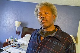 Abel Currie, 63, sits in his hotel room in May quarantined safely as he searches for a permanent apartment.