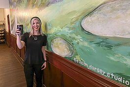 Artist Eileen Dorsey toasts the finish of her new mural at Flannery's Pub