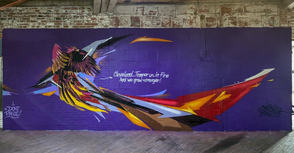"Temper Us in Fire, is the newest mural created by artists Bob Peck and R!ch Cihlar who paint together under the name ""Don't Panic!""."