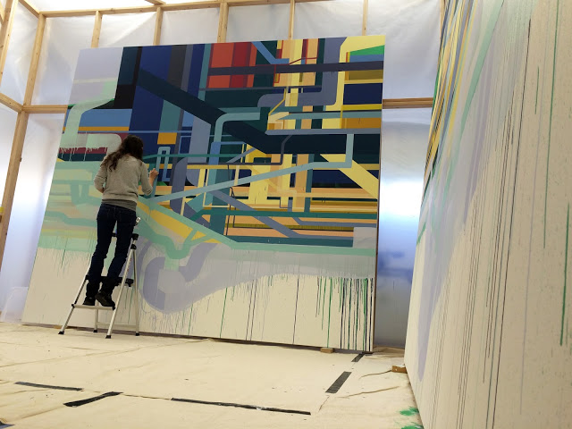 "Dana Oldfather works on one of two ""Reflexive"" panels"