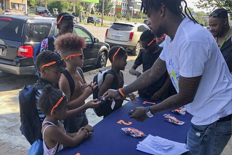 Craven Smith gives kids wristbands and sunglasses with anti-bullying messages on them.