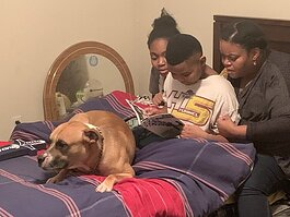 Arrington reading comics with 11-year-old daughter Michaela; 10-year-old son Michael, Jr.; and dog Buster